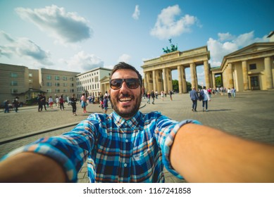 Berlin, Germany, a happy tourist with sunglasses take selfie photo in front of the Brandenburg Tor Gate. Summer, holidays, vacation and happiness concept