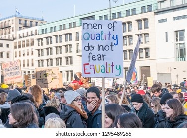 """Berlin, Germany - Januar 19, 2019:  2019 Women's March in Berlin.  Woman in crowd holds a banner saying """"Men of quality do not fear Equality"""". March supports Womens rights and fights for equality."""