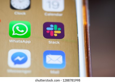 BERLIN, GERMANY - JANUARY 19, 2019: Close up to new Slack team chat app on the screen of an iPhone 7 Plus with personalized background.