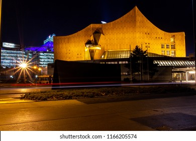 BERLIN, GERMANY - JANUARY 25, 2012: Long exposure night shot of the modernist Berliner Philharmonie, house of the Berlin Philharmonic Orchestra, with Potsdamer Platz at the back while car passes by.