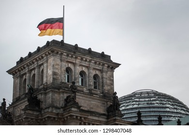 Berlin, Germany - January 27th, 2019: International Holocaust Remembrance Day. The German flag is flown at half mast at the Reichstag building.