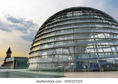 Berlin, Germany - Jul 2010: Reichstag dome exterior in summer. Yellow sunlight reflection on glass window. Popular tourist attraction. Cloud in blue sky.