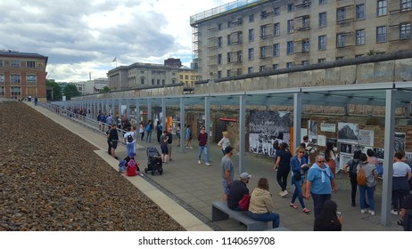 BERLIN, GERMANY - JULY 1, 2018: Tourists along the Berlin Wall remains in Berlin, Germany.