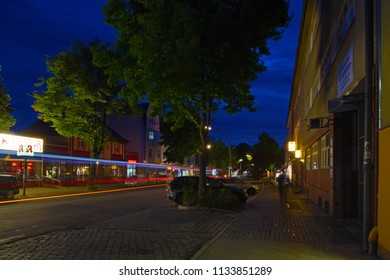 Berlin, Germany - July 12, 2018: Long exposure of a night scene of a village shopping street in Berlin with rays of light from a passing bus.