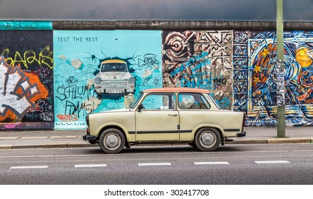 BERLIN, GERMANY - JULY 12: Berliner Mauer (Berlin Wall) at East Side Gallery with an old Trabant, the most common car used in East Germany, on July 12, 2015 in Berlin Friedrichshain-Kreuzberg, Germany