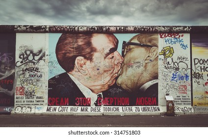 BERLIN, GERMANY - JULY 12: Street art graffiti painting 'The Kiss' by Dmitri Vrubel at famous East Side Gallery with retro vintage Instagram style filter effect on July 12, 2015 in Berlin, Germany.