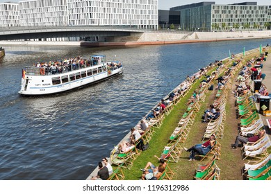 BERLIN, GERMANY - JULY 13, 2018: Captain Morgan touristic ship with passengers sailing along Spree river in front of popular Capital Beach club on a hot summer day in Mitte city district.
