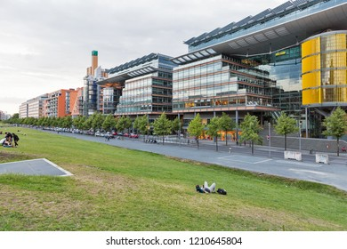 BERLIN, GERMANY - JULY 13, 2018: Unrecognized people have a rest in Tilla Durieux Park in front of Potsdamer Platz Arkaden mall. Berlin is the capital and German largest city by area and population.