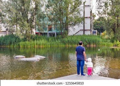 BERLIN, GERMANY - JULY 13, 2018: Unrecognized father and child at Piano Lake shore in front of German Society for International Cooperation building close to Potsdamer Platz.