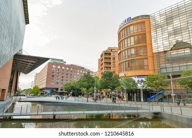 BERLIN, GERMANY - JULY 13, 2018: People walk at Marlene Dietrich Platz with Stage Theater at Potsdamer Platz and Stage Theater Bluemax. Berlin is the capital and largest city of Germany.