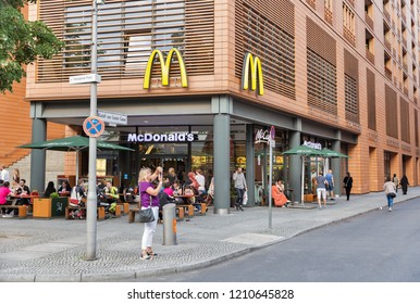 BERLIN, GERMANY - JULY 13, 2018: People enjoy food in McDonald's restaurant in downtown. It is an American fast food company, founded in 1940 as a restaurant operated by Richard and Maurice McDonald.