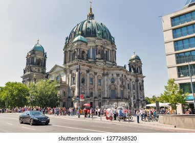 BERLIN, GERMANY - JULY 14, 2018: People walk in front of Berliner Dome Cathedral and Liebknecht Bridge over Spree river. Berlin is the capital and German largest city.