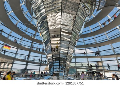 BERLIN, GERMANY - JULY 14, 2018: People walk inside the Reichstag dome, second most visited attraction in Germany. Huge glass dome was erected on the roof as a gesture to the original 1894 cupola.