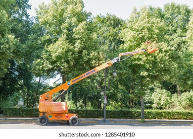 BERLIN, GERMANY - JULY 14, 2018: Herrmann and Wittrock mobile lifting platform crane for tree trimming in Tiergarten park close to Brandenburg Gate. Berlin is the capital and largest city of Germany.