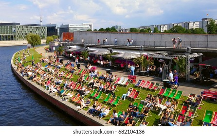 BERLIN, GERMANY - JULY 15, 2017: People relaxing in Spree riverside, having fun and enjoying some drinks in a sunny day
