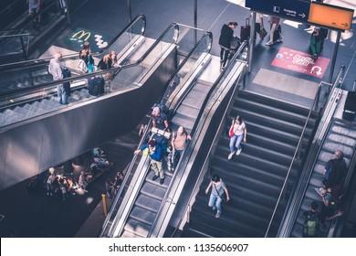 Berlin, Germany - july 2017: Traveling people with luggage on escalator inside main train station (Hauptbahnhof)   in Berlin, Germany