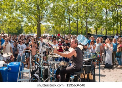 Berlin, Germany - july 2018: Many people in crowded Park (Mauerpark) watching  street performing / musician playing the drums on a sunny summer sunday in Berlin, Germany
