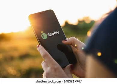 BERLIN, GERMANY JULY 2019: Woman holding a iPhone Xs opening spotify app, Spotify is a music service that offers legal streaming music.