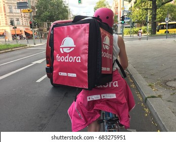 Berlin, Germany - July 21, 2017: Back turned Foodora delivery woman at work. Foodora GmbH is a Berlin-based online food delivery company