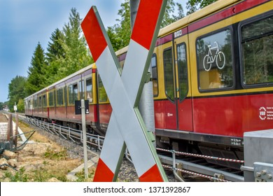 Berlin, Germany - July 22, 2018: Traffic sign at a railroad crossing. In the background you can see a train from the company Deutsche Bahn.