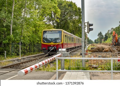 Berlin, Germany - July 22, 2018: Scene at a Berlin railroad crossing with closed barrier, which is passed by a train of the company Deutsche Bahn.