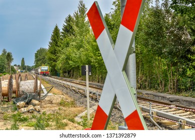 Berlin, Germany - July 22, 2018: Unfocussed traffic sign at a railroad crossing. In the background you can see a train from the company Deutsche Bahn.