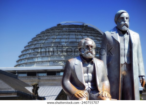 BERLIN, GERMANY - JULY 25, 2012: the Monument of Marx and Engels in the city center Berlin, the Reichstag in the background
