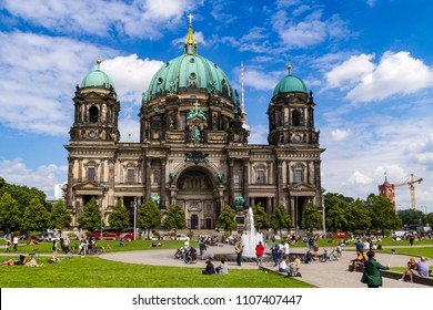 Berlin, Germany - July 27, 2017: Colorful panoramic view of Berlin Cathedral Berliner Dom and tourists relaxing near the Cathedral. Beautiful blue sky.