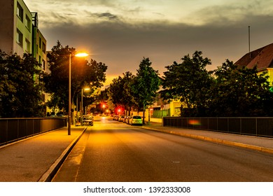 Berlin, Germany - July 27, 2018: Night shot of a side street with lit lanterns, traffic lights and star-shaped halos