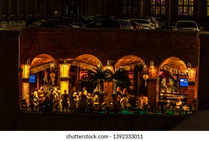 Berlin, Germany - July 27, 2018: Cocktail bar under a parking lot in a historic building in Berlin, Germany. One side is built open and allows the view of the celebrating guests from the outside.