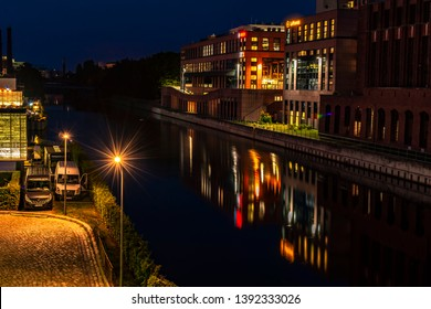 Berlin, Germany - July 27, 2018: Night shot of a harbor on the Teltow Canal in Berlin-Tempelhof with old warehouses. There are also restaurants with colorful lights.