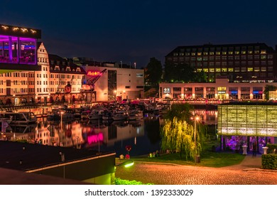Berlin, Germany - July 27, 2018: Night shot of a harbor on the Teltow Canal in Berlin-Tempelhof with boats, old warehouses and cranes. There are also restaurants with colorful lights.