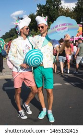 BERLIN, GERMANY - JULY 27, 2019: Gay pride, or Christopher Street Day, Two men in unicorns costumes. The poster says: this is not a fairy tale, we exist