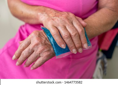 Berlin, Germany – July 29, 2019 Hands of an elderly woman with a cold compress