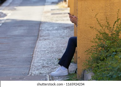 BERLIN, GERMANY – JUNE 07, 2018: young woman sitting on a step in Berlin and typing on the smartphone