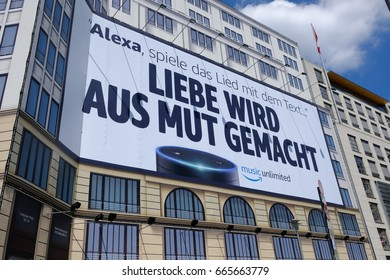"Berlin, Germany - June 19, 2017: Amazon Alexa advertisement signboard. The new function of Amazon understands song lyrics from the music. The written German text means ""Love is made of courage"""