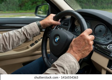 Berlin, Germany – June 2, 2019 Hands of a man on a steering wheel in a BMW sports car