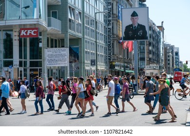 Berlin, Germany - june 2018: People  at Checkpoint Charlie  on a sunny summer day in Berlin, Mitte.  The former border Checkpoint is one of the most  famous landmarks in Berlin