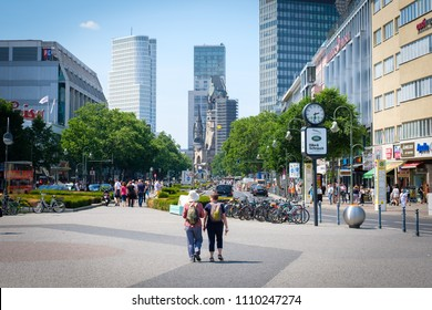 Berlin, Germany - june  , 2018: Two traveler with backpacks on Berlin`s famous shopping avenue Kurfuerstendamm a.k.a. Kudamm in Berlin, Germany