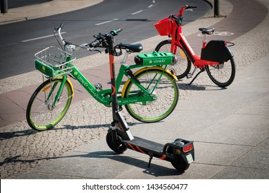 Berlin, Germany - June, 2019: Bike sharing bicycles and electric scooter , escooter or e-scooter on sidewalk in Berlin, Germany
