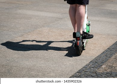 Berlin, Germany - June, 2019: Man riding an electric scooter , escooter or e-scooter of the ride sharing company LIME on sidewalk in Berlin, Germany