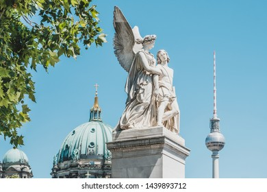 Berlin, Germany - June, 2019: The statue Nike assists the wounded warrior with TV tower (Fernsehturm) and Berlin Cathedral in background