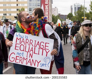 BERLIN, GERMANY - JUNE 21, 2014:Christopher Street Day.An unidentified gays kissing during Gay pride. Crowd of people participate in the parade celebrates gays, lesbians, bisexuals and transgenders.