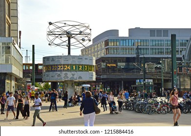 BERLIN, GERMANY - JUNE 21, 2017: people in Berlin's Alexanderplatz square with the Weltzeituhr (World Time Clock). Alexanderplatz is also an important central transportation hub of Berlin, Germany