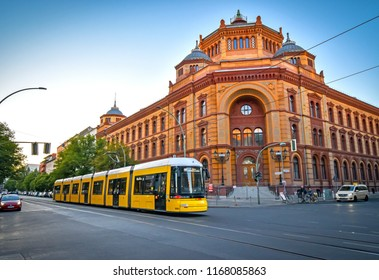 Berlin, Germany - June 30, 2018: View of a large intersection with a historic post office in Berlin Mitte, Germany, with a tram in the foreground in the evening sun.