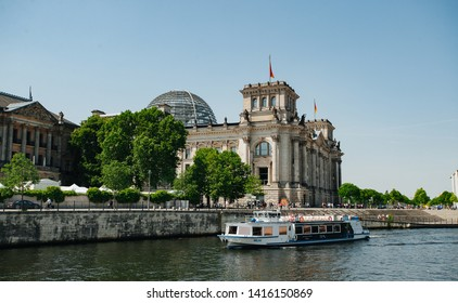 Berlin, Germany - June 4, 2019: Tourist boat doing sightseeing tour on river Spree at German Reichtag building and Paul Löbe Haus in Berlin