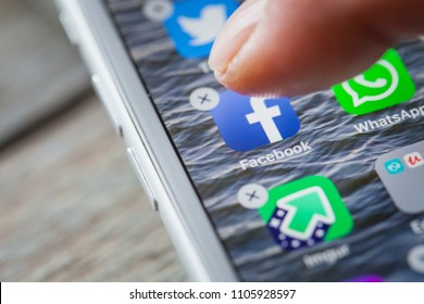 BERLIN, GERMANY - JUNE 6, 2018: Close up to finger deleting the Facebook app on the screen of an iPhone 7 Plus with personalized background.