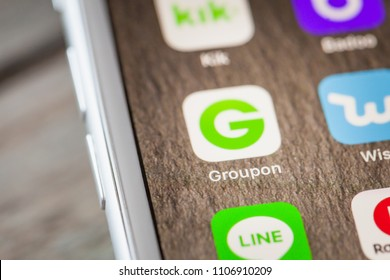 BERLIN, GERMANY - JUNE 6, 2018: Close up to Groupon discount offer app on the screen of an iPhone 7 Plus with personalized background.