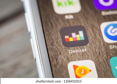 BERLIN, GERMANY - JUNE 6, 2018: Close up to Deezer music streaming app on the screen of an iPhone 7 Plus with personalized background.