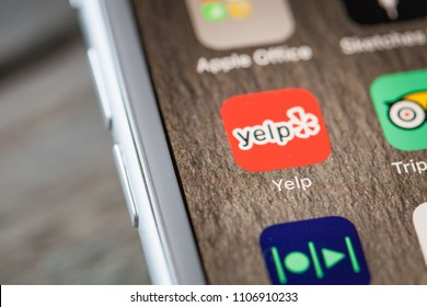 BERLIN, GERMANY - JUNE 6, 2018: Close up to service review app Yelp on the screen of an iPhone 7 Plus with personalized background.